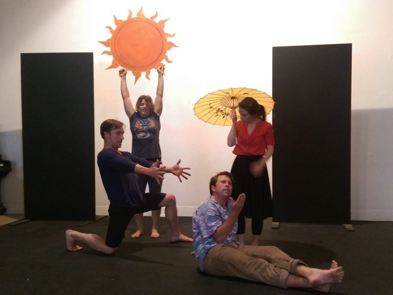Four actors arranged in a beach scene: one holds a painted sun, one a yellow parasol, and one kneels with arms outstretched toward another who is sunning himself and relaxing.