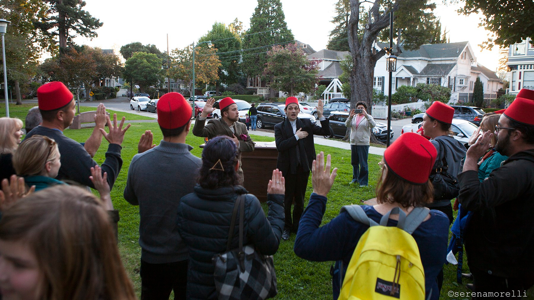 Audience and actors, many wearing red fezzes, recite a pledge holding one hand on their hearts and another in the air.
