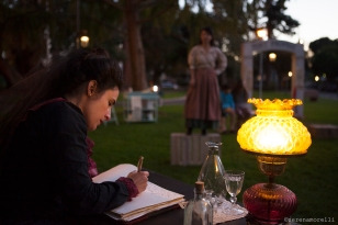 Josephine (Maria A. Leigh) writes in her room as Anita (Kristin Matia) looks on in an evening scene from Elixir of Life (2017). Photo by Serena Morelli.
